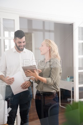 Man and woman in an office using a pc tablet