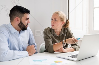Man and woman looking at each other at a desk