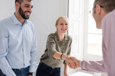 Man and woman shake hands and smile