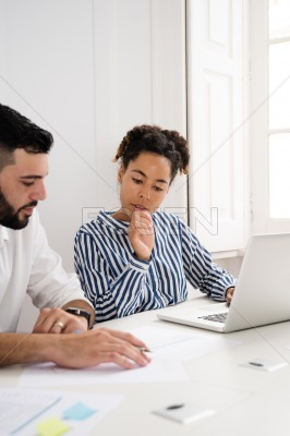 Man and woman sitting at a laptop talking