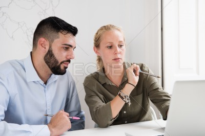 Pensive looking man and woman sit behind a desk