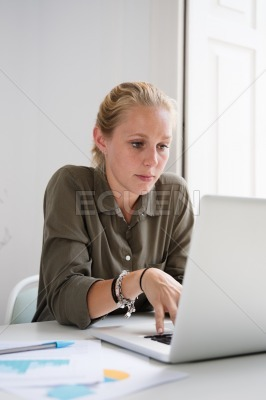 Seated woman leans forward while working