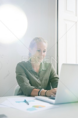 Seated woman smiles as she types on a laptop