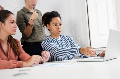 Three woman sitting in front of a laptop
