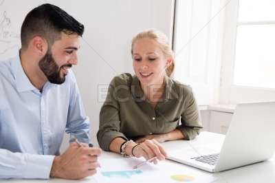Woman and man sit behind a desk and smile