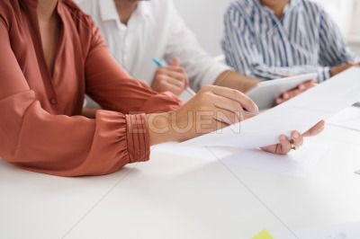 Woman holds a document in her hand as points