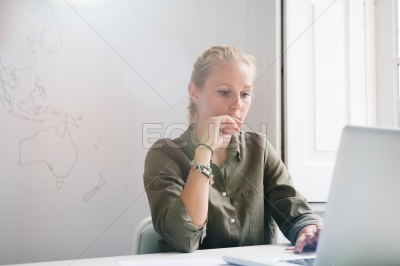 Woman looking thoughtfully at laptop as she works