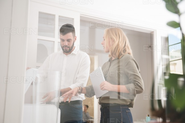 Business colleagues standing around the copier stock photo