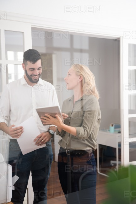 Man and woman in an office using a pc tablet stock photo