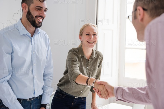 Man and woman shake hands and smile stock photo