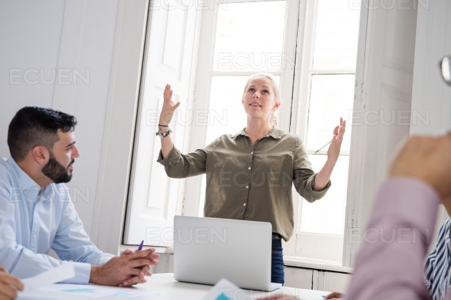 Woman stands in an office with lifted hands