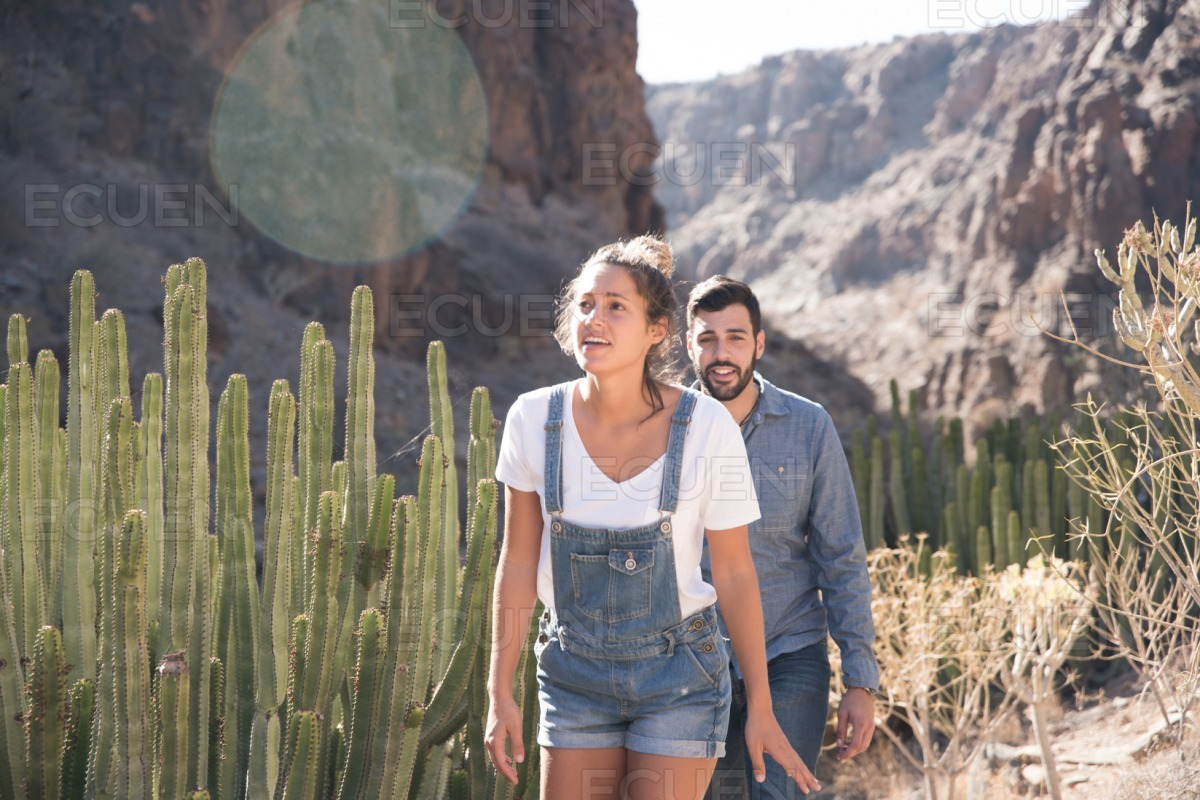 Couple walking past cactus in the mountains stock photo