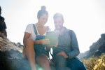 Couple sitting on a rock looking at a pc tablet