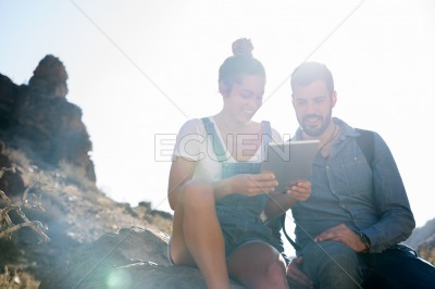 Couple sitting on a rock lauging
