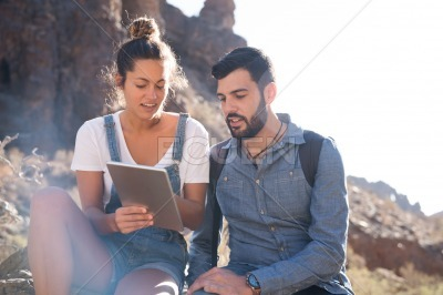 Couple talking as they look at a pc tablet