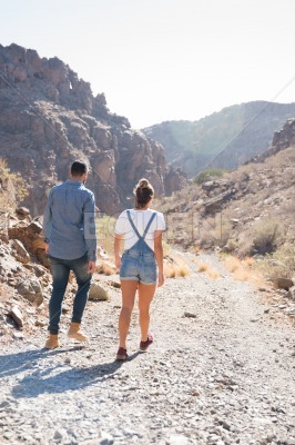 Couple walking down a rocky path in the mountain