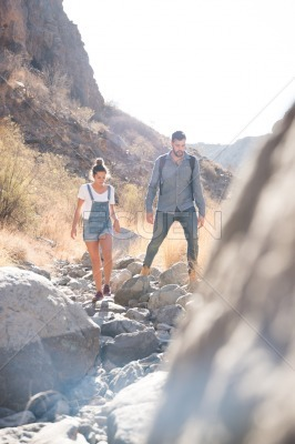 Couple walking over a rocky path