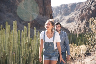 Couple walking past cactus in the mountains