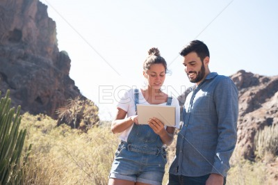 Man and woman looking at a pc tablet and smiling