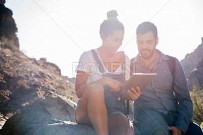 Man and woman sitting on a rock smiling