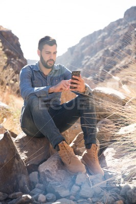 Man seated on a rock and texting