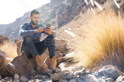 Man sitting on a rock texting on a cell phone