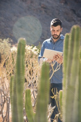 Man standing ext to tall brown grass texting