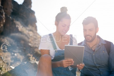 Smiling man sits next to a woman on a rock