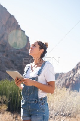 Woman holding pc tablet as she looks up at the sky