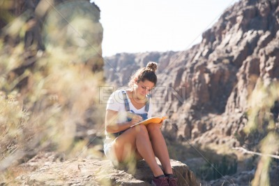 Woman looking down and writing in a book