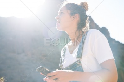 Woman looks up from her cell phone in the mountain