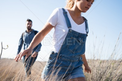 Woman running through long grass with her arms out