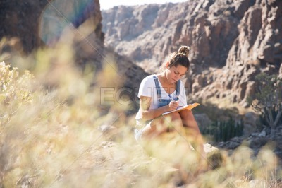 Woman writing in a book in the mountains