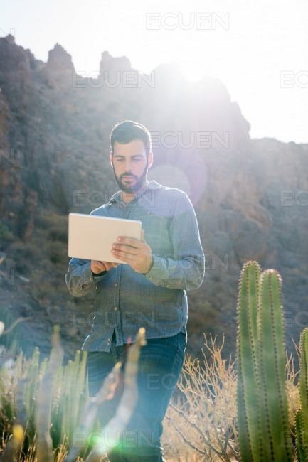 Man standing next to a mountain and a cactus