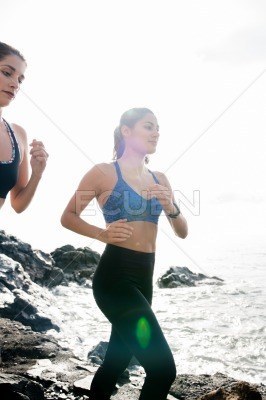 Two women running with the ocean in the background