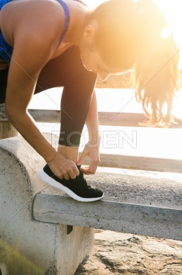 Woman bends over a bench and ties her shoe