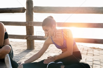Woman in blue crop top doing stretching excersises