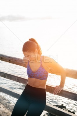 Woman leans with her back against a fence