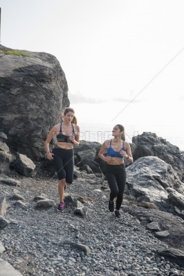 Women running and talking on the beach