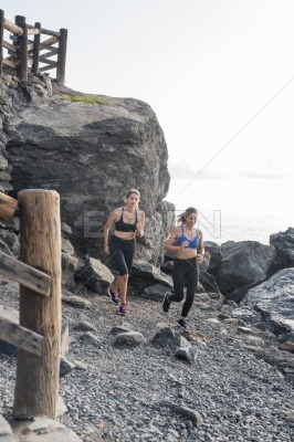 Women running on a beach with boulders in the back