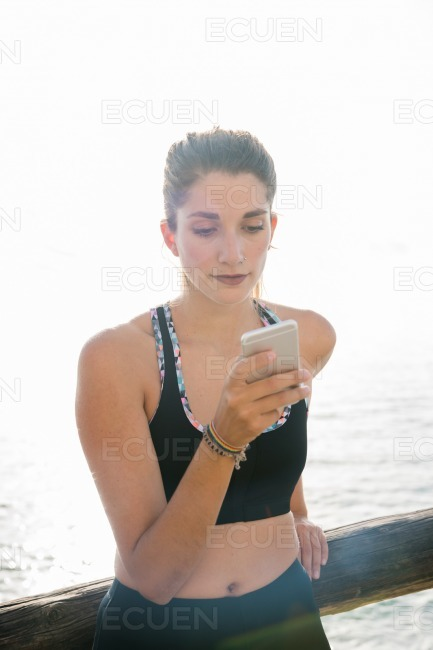 Woman looking at her phone at the beach stock photo