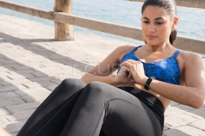 Woman doing sit ups on the sidewalk by a fence