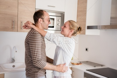 Couple holding each other in the kitchen