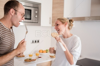 Couple in the kitchen singing and laughing