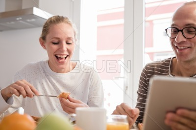 Couple laughing as they eat breakfast at a table