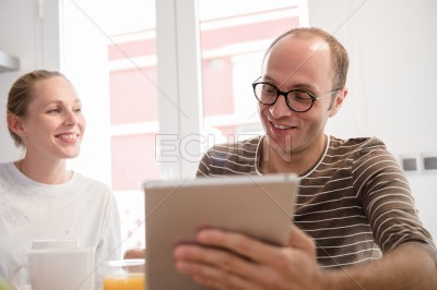 Couple laughing at a table as they look at a pc
