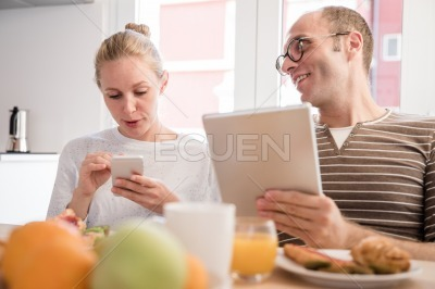 Couple laughing at a table they look at technology