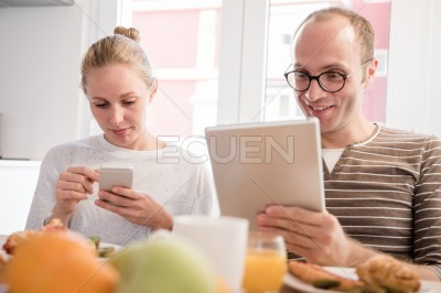 Couple looking down at their technology at a table