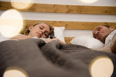 Couple lying in a bed as they sleep