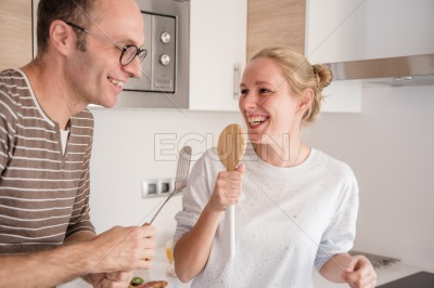 Couple singing and laughing in the kitchen